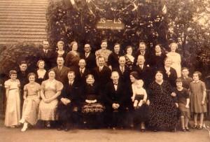 Guldbryllupsbillede med Johanna og Lars Kristian siddende i midten med familiemedlemmer omkring sig